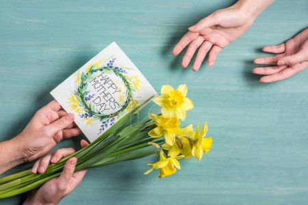 Photo for Partial view of man presenting greeting card and daffodils to woman at mothers day - Royalty Free Image