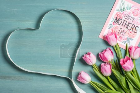 Photo for Beautiful pink tulips with happy mothers day greeting card and heart shaped ribbon - Royalty Free Image