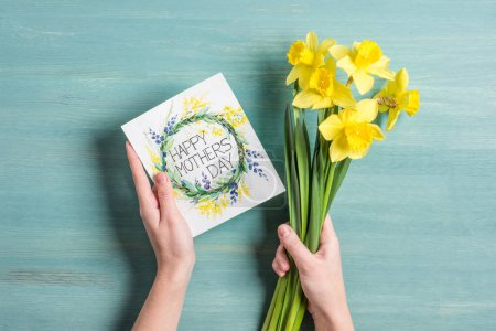 Photo for Top view of happy mothers day greeting card and yellow daffodils in hands - Royalty Free Image