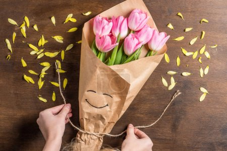 Foto de Top view of beautiful pink tulips bouquet with smiling face on wrapping paper for Mother's day holiday gift, yellow petals on wooden table and hands holding rope - Imagen libre de derechos
