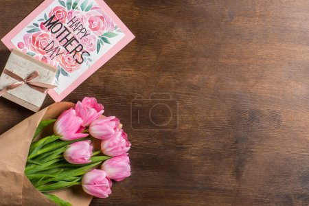 Photo for Top view of beautiful pink tulips bouquet in wrapping paper, happy mothers day postcard and gift on wooden table - Royalty Free Image