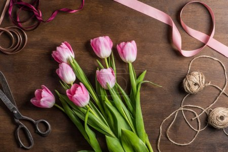 Photo for Top view of beautiful pink tulips on wooden table with ribbons, ropes and old scissors for making Mothers day bouquet - Royalty Free Image