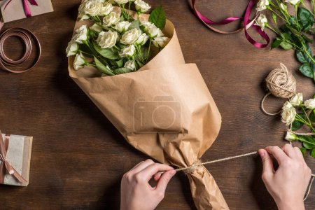 Foto de Top view of holiday preparation with hands tying rope on white roses bouquet in wrapping paper - Imagen libre de derechos