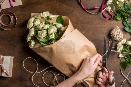 Photo for Top view of holiday preparation with hands cutting rope with old scissors for white roses bouquet in wrapping paper - Royalty Free Image
