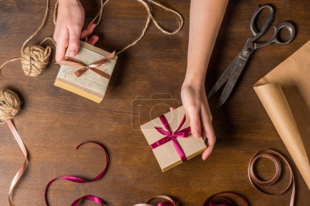 Foto de Top view of hands holding small gifts for holiday with old scissors, ribbons and ropes on wooden table - Imagen libre de derechos