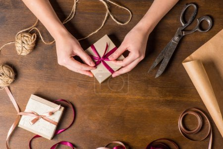 Foto de Top view of hands tying ribbon on gift with old scissors and ropes on wooden table, holiday preparation concept - Imagen libre de derechos