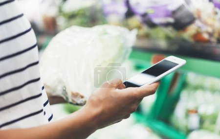 Young woman shopping healthy food in supermarket blur background.
