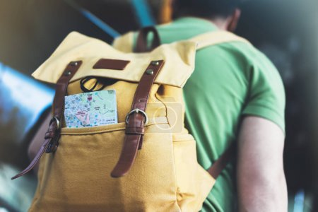 Hipster young man with backpack and map.