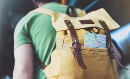 Hipster young man with backpack and map