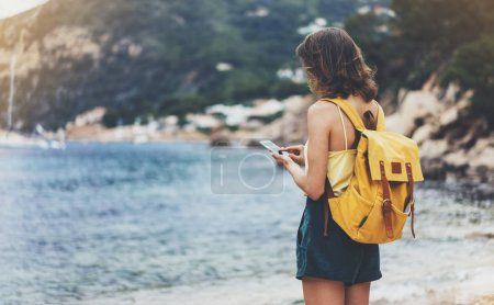 Photo for Hipster girl with backpack hold on smart phone gadget in sand coastline, mock up. Traveler using in female hand mobile on background beach seascape horizon. Tourist look on blue sun ocean, summer lifestyle - Royalty Free Image