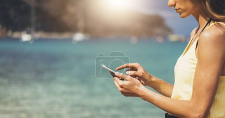 Photo for Hipster girl hold on smart phone gadget in sand coastline, mock up blank screen. Traveler using in female hand mobile on background beach seascape horizon. Tourist look on blue sun ocean, summer lifestyle - Royalty Free Image