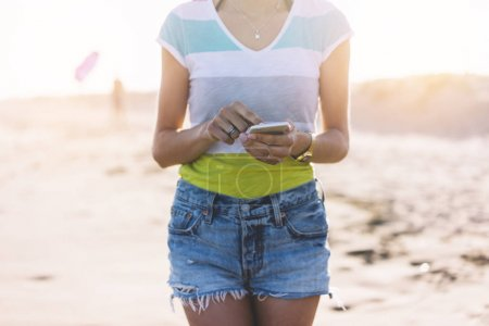 Hipster girl photograph on smart phone gadget in sand coastline beach, mock up of blank screen. Traveler hold and using in female hand mobile on background seascape horizon. Tourist look on blue sun ocean