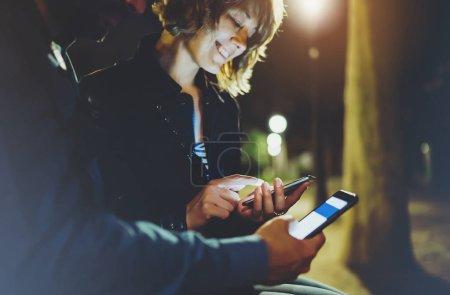 Photo pour Les gens pointant ensemble doigt sur écran smartphone sur fond bokeh lumière dans la nuit ville atmosphérique, groupe adultes amis hipsters en utilisant dans les mains téléphone portable moderne gros plan, rue concept internet wi-fi en ligne - image libre de droit