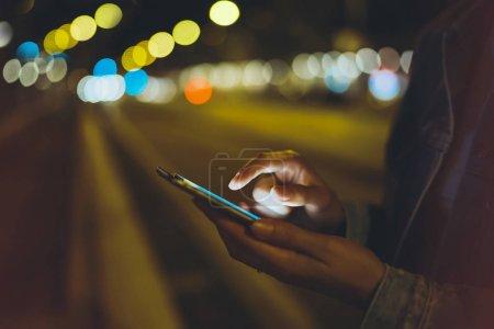 Chica señalando el dedo en la pantalla del teléfono inteligente en la iluminación de fondo resplandor bokeh luz en la ciudad atmosférica noche, hipster usando en las manos teléfono móvil, farolas de la calle, concepto de Internet en línea