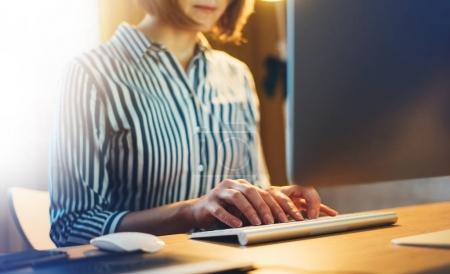 Foto de Las mujeres de negocios que trabajan en la oficina con la computadora del monitor en la noche, gerente hipster joven escribiendo en el teclado, las manos femeninas mensaje de texto, concepto de proceso de trabajo en el lugar de trabajo de coworking, concepto de proyecto de puesta en marcha - Imagen libre de derechos