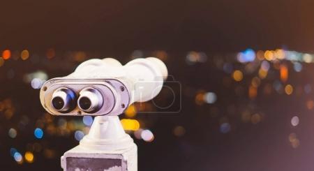 Telescopio turístico mira a la ciudad con vista a Barcelona España, cerca de binoculares metálicos antiguos en el punto de vista de fondo, moneda hipster operado en observación de panorama, bengalas simuladas, iluminación bokeh luz en el cielo atmosférico desenfoque noche