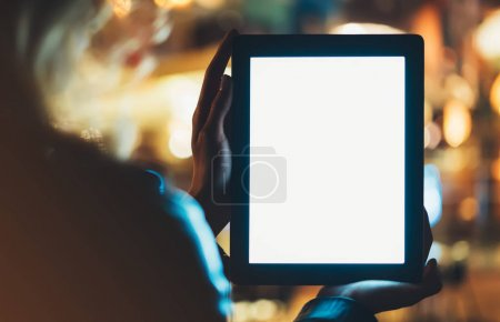 Girl holding in hands on blank clean screen tablet on background illumination glow bokeh light in night atmospheric city, hands using template mobile computer on lights glitter street; mockup gadget