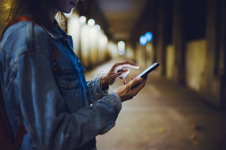 Photo for Woman pointing finger on blank screen smartphone on background bokeh light in night atmospheric city, hipster blogger using in hands clean gadget mobile phone, mockup street, online wifi internet concept - Royalty Free Image