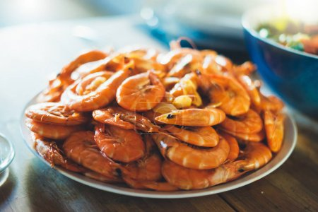 Isolated prepared orange shrimp on background table on kitchen, closeup of fresh prawn products in restaurant, shellfish sea food on plate, group cooked boiled seafood, ocean dieting shrimps on cuisine