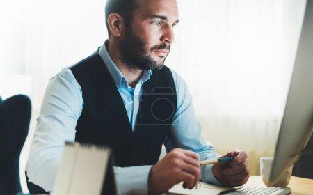 Photo pour Homme pensant regarder dans l'ordinateur de moniteur au travail à la maison. distance sociale barbu homme d'affaires travaillant au bureau, consultant financier en ligne concept de processus de travail Internet, étude étudiant éducation en ligne - image libre de droit