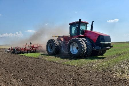 Tractor working in a field, agricultural machinery in the work,