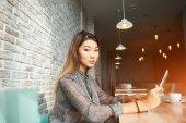 Female financier is reading financial news in internet via touch pad