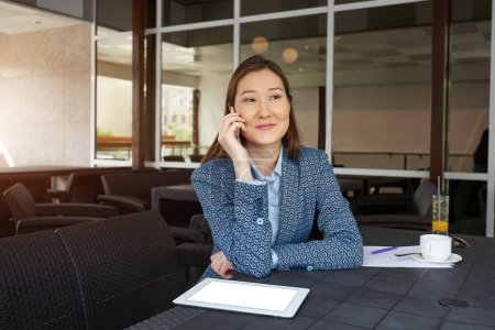 Kazakh business woman calling with cell telephone