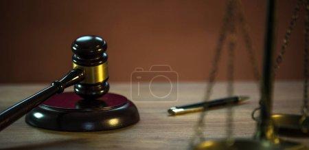 Photo pour Balances et marteau sur fond de table en bois avec espace de reproduction - image libre de droit
