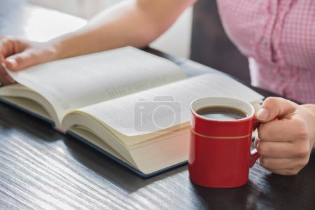 Woman hands holding open book with pile of closed books and cup of coffee home..