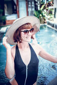 Beauty sexy woman with hat and sunglasses enjoying her summer vacation at swimming pool on a luxury villa. Summer holiday idyllic. Tropical Bali island, Indonesia.
