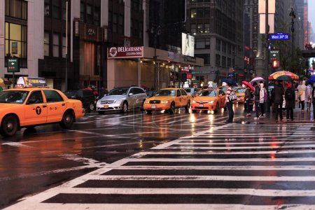 Photo for New York, USA - May 20, 2013: taxi's crossing at Time Square at night in the rain. The site is regarded as the world's most visited tourist attraction with nearly 40 million visitors annually. - Royalty Free Image