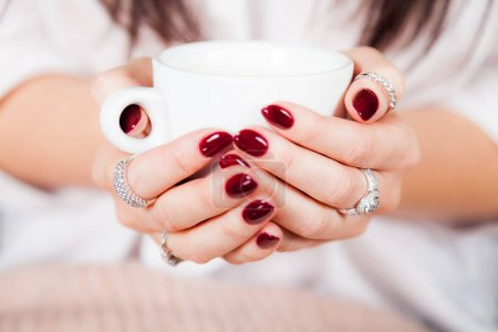 Closeup front view of female hands holding a cup of coffee