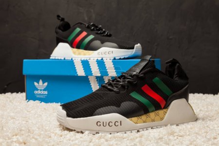New beautiful colorful and nice Adidas Gucci running shoes, sneakers, trainers showing the logo with a brand box on abstract background. Sport and casual footwear concept. Kyiv, Ukraine-May 15, 2018