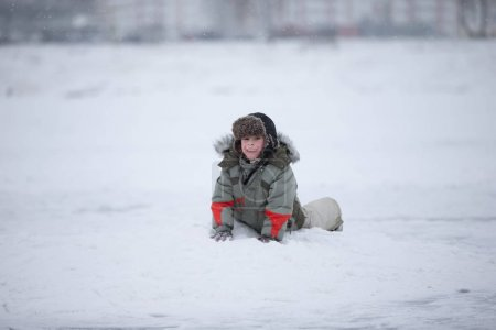 A child is joyful playing in the snow. A boy in winter with a fur hat