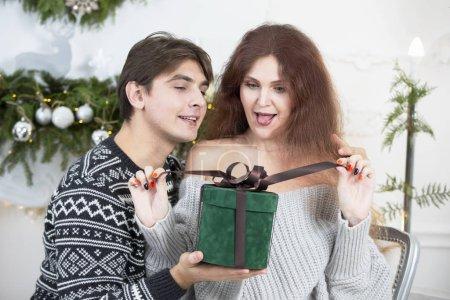 Photo pour Un homme offre un cadeau de Noël à une femme. Époux et épouse pendant les vacances du Nouvel An. Prenez une surprise pendant les vacances d'hiver. Concept de vacances de Noël. - image libre de droit