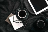 Tablet and coffee on gray woolen plaid