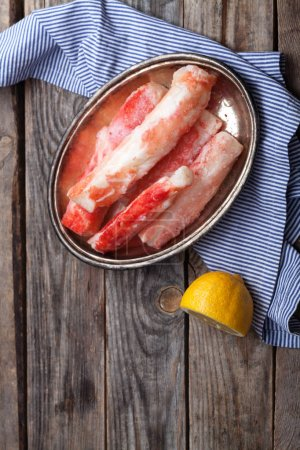 Photo for Fresh uncooked crab phalanx on vintage tray on rustic gray wooden background with lemon half - Royalty Free Image
