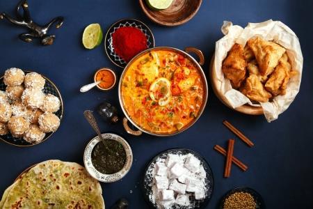 Photo pour Cuisine indienne pendant les vacances de diwali : tikka masala, samosa, galettes et bonbons avec chutney à la menthe et épices. Fond bleu foncé - image libre de droit
