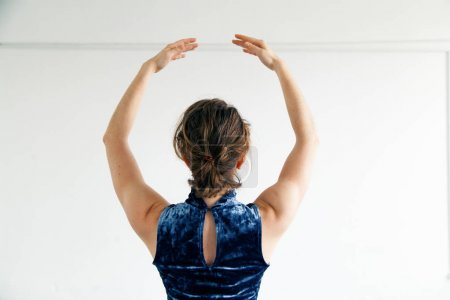 Young female performer dressed in blue velvet dress practicing contemporary dance elements in white spacious loft. View from behind. Natural lighting. Horizontal composition with copy space.