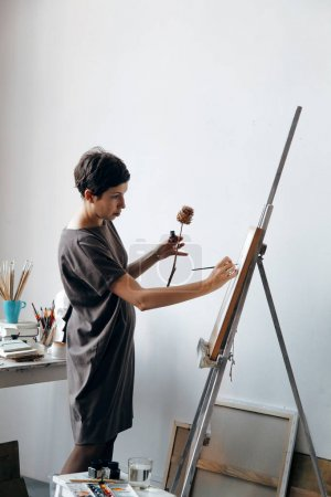Female artist in her spacious white studio working with watercolor painting.  Natural lighting. Disclosure of creativity concept. Vertical composition with copy space