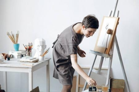 Female artist in her spacious white studio working with watercolor painting dipping a brush into glass with water.  Natural lighting. Disclosure of creativity concept. Horizontal composition.