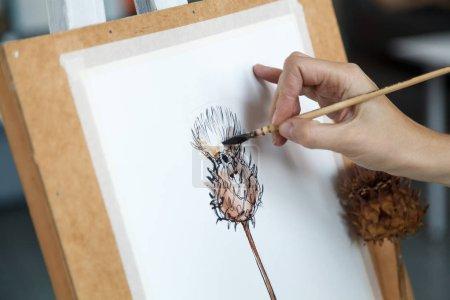 Female artist creating watercolor image of decorative artichoke. Natural lighting. Disclosure of creativity concept. Horizontal composition.