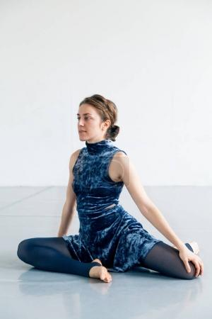 Young female performer practicing contemporary dance elements in white spacious loft. Natural lighting. Vertical composition, copy space.