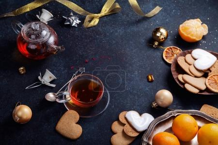 Teatime with heart-shaped ginger cookies and tangerines. Christmas background with festive decoration. Horizontal composition