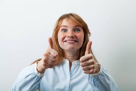 pretty and funny red-headed woman smiling and showing thumbs up feeling enthusiastic and satisfied with good offer