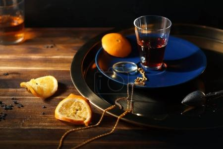 glass with black turkish tea on blue plate with golden magnifier on chain and squeezed orange slices on wooden table