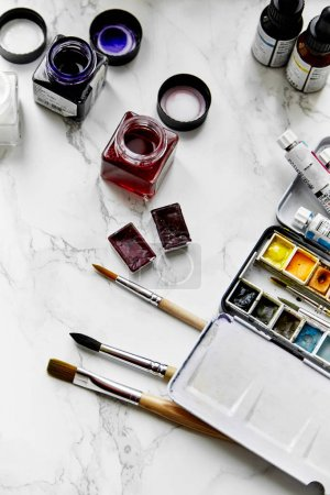 artist workplace with paints and brushes with watercolor,  top view