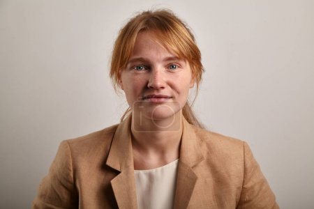 young redheaded woman with freckles and ponytail hairstyle wearing beige jacket and looking at camera with serious expression, student concept