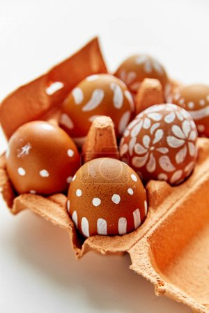 painted eggs in various white patterns in colorful orange cardboard container, Easter holiday concept