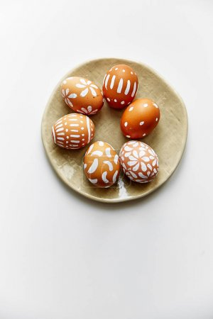 plate with white painted eggs with various patterns isolated on white background, Easter holiday concept